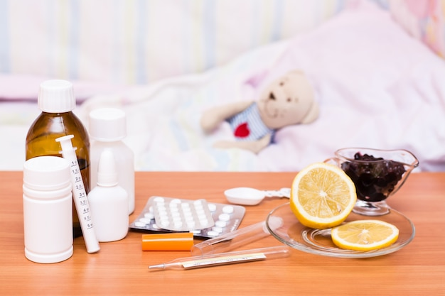Medicines on the table  children's bed with a soft toy