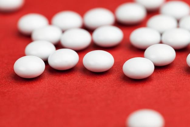 薬に使われる薬、錠剤の病気の治療のための活性物質の投与量、赤い背景に散らばっている病気の治療のための薬