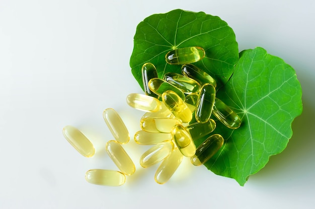 Medicines and treatment, healthcare. fish oil capsules on the green leaves.