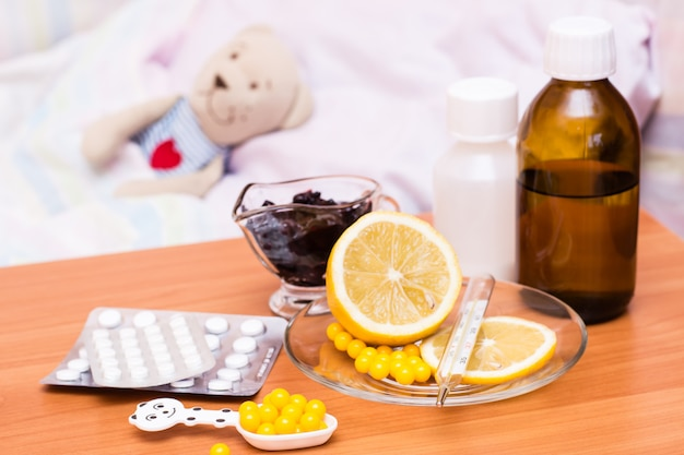Medicines, vitamins, lemon and jam on the table  children's bed with a soft toy