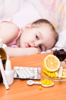 Medicines and vitamins on the table  child in a bed that has chickenpox