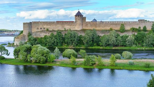 Средневековый замок у реки с большой оборонительной стеной и каменными башнями.