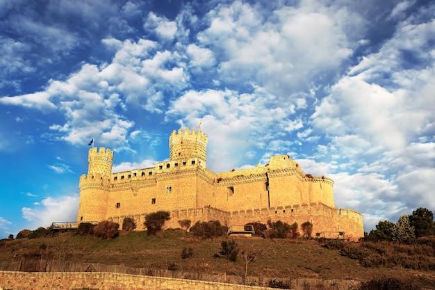 山の上の中世の城、旗、青い空と雲の塔。カスティージョマンサナレスレアルマドリード。ヨーロッパ