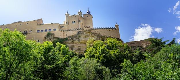 Средневековый замок на вершине горы с зеленой растительностью и голубым небом