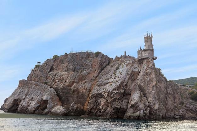 Средневековый замок ласточкино гнездо расположен на вершине скалистого обрыва среди черного моря. известный ориентир старой башни в крыму, россия.