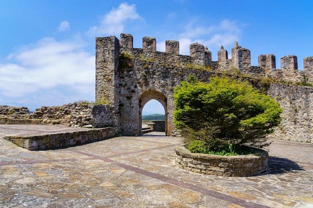 Средневековый замок с каменной стеной и арочными входными воротами в солнечный день