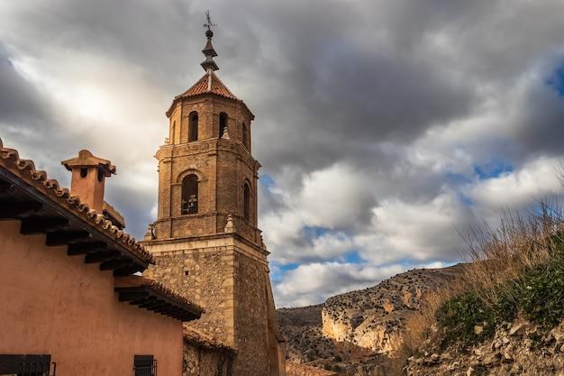 曇り空の背景と街の石造りの屋根の上に太陽フレアを持つアルバラシンの街の中世の教会。テルエルスペイン。ヨーロッパ。