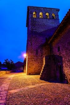 夜に街灯柱で照らされた中世の教会塔。サンティリャーナデルマールサンタンデール。