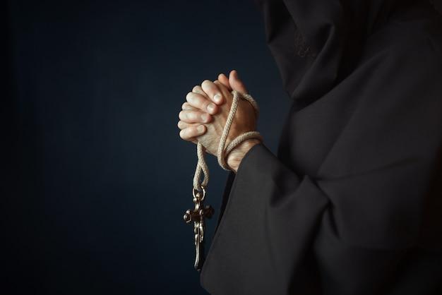 Средневековый монах молится с деревянным крестом в руках в церкви, секретный ритуал. таинственный монах в темной накидке. тайна и духовность