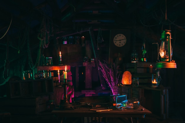 Medieval interior of the mystical laboratory of an alchemist witch with candles and various potions in flasks