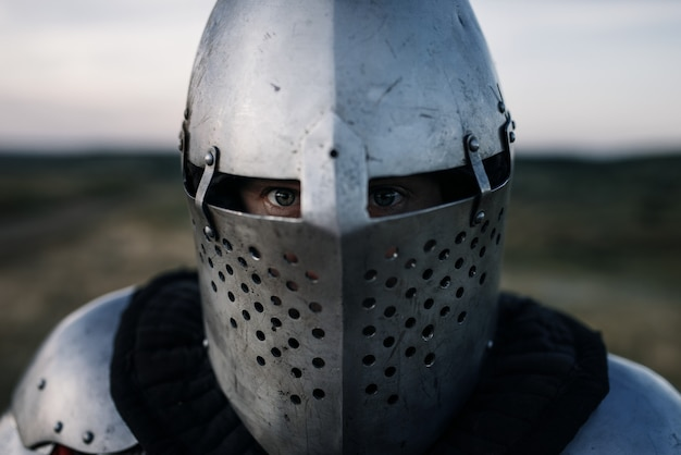 Medieval knight in armor and helmet closeup view, great battle. armored ancient warrior in armour posing in the field