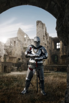 Medieval knight in armor and helmet poses in castle, great battle. armored ancient warrior in armour posing in the field