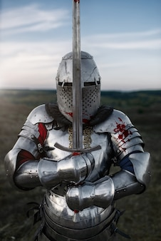 Medieval knight in armor and helmet poses with sword, great battle. armored ancient warrior in armour posing in the field