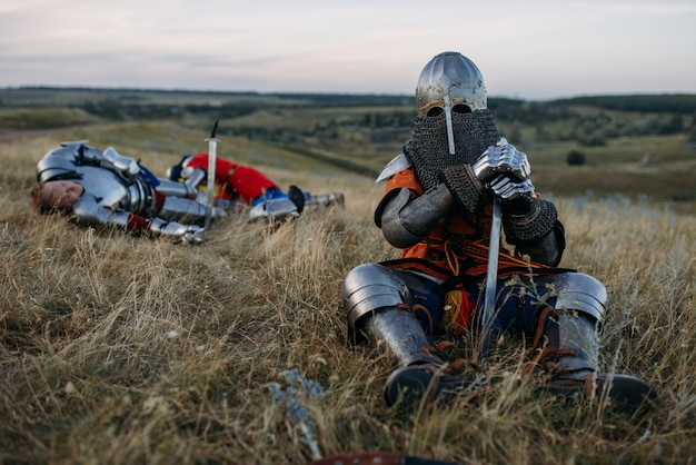Medieval knight in armor and helmet sitting on the ground after great battle. armored ancient warrior in armour posing in the field