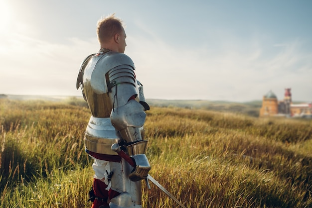 Medieval knight in armor holds sword. armored ancient warrior in armour posing in the field