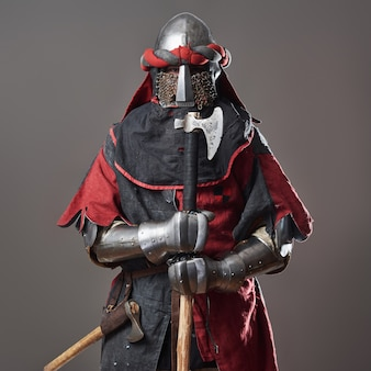 Medieval knight on grey. portrait of brutal dirty face warrior with chain mail armour red and black clothes and battle axe