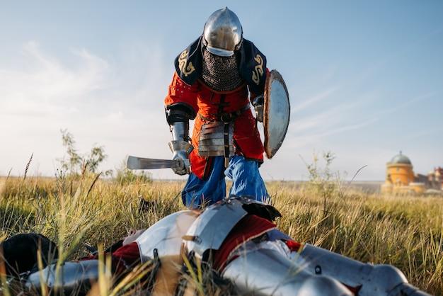 Средневековый рыцарь в доспехах и шлемах приставил меч к горлу противника. бронированный древний воин в доспехах позирует в поле