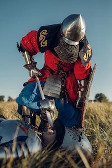 Средневековый рыцарь в доспехах и шлемах приставил меч к горлу соперника, великий турнир. бронированный древний воин в доспехах позирует в поле