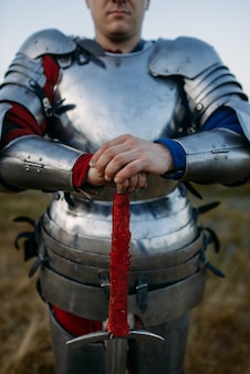 Medieval knight in metal armor holds sword, great battle. armored ancient warrior in armour posing in the field
