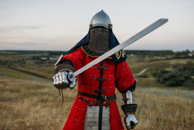 Medieval knight in metal helmet holds sword, great battle. armored ancient warrior in armour posing in the field