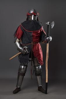 Средневековый рыцарь на сером фоне. портрет жестокого воина с грязным лицом в красной и черной одежде кольчужных доспехов и боевого топора.