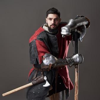 Средневековый рыцарь на сером фоне. портрет жестокого воина лица с кольчужной броней красно-черной одеждой и боевым топором.