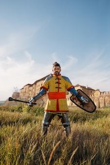 Средневековый рыцарь позирует в доспехах напротив замка, грандиозный турнир. бронированные древние воины в доспехах позируют в поле