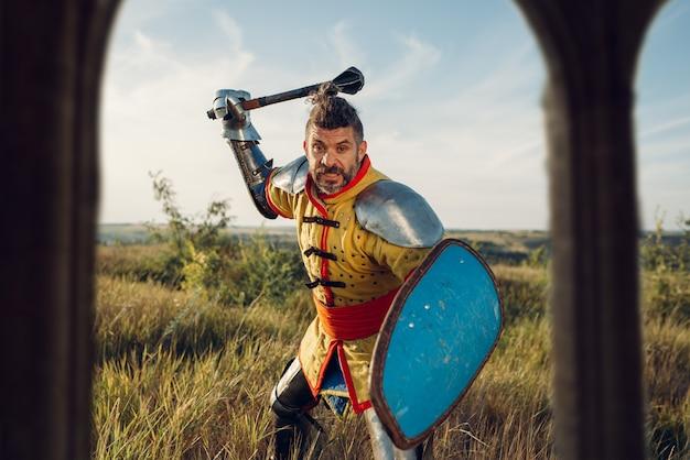 中世の騎士が城の向かいの鎧でポーズをとる