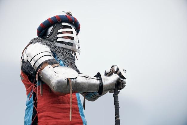 Средневековый рыцарь позирует с мечом