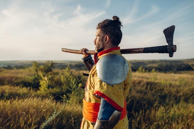 Средневековый рыцарь с топором позирует в доспехах напротив замка, великий бой. бронированные древние воины в доспехах позируют в поле