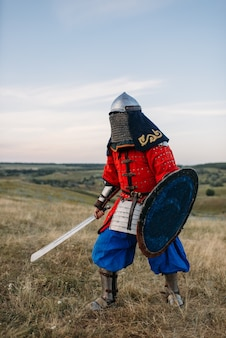 Medieval knight with sword poses in armour, great fighter. armored ancient warriors in armor posing in the field