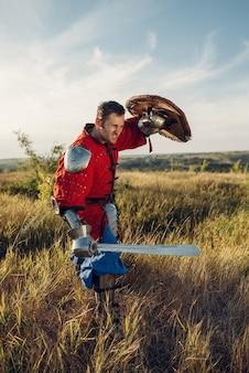 Средневековый рыцарь с мечом позирует в доспехах напротив замка, грандиозный турнир. бронированные древние воины в доспехах позируют в поле