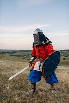 Средневековый рыцарь с мечом в доспехах, великий боец. бронированные древние воины в доспехах позируют в поле