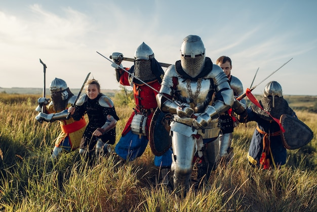 Medieval knights in armor and helmets fight with sword and axe, great tournament. armored ancient warrior in armour posing in the field