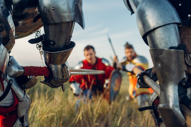 Medieval knights in armor standing opposite each other before battle. armored ancient warrior in armour posing in the field