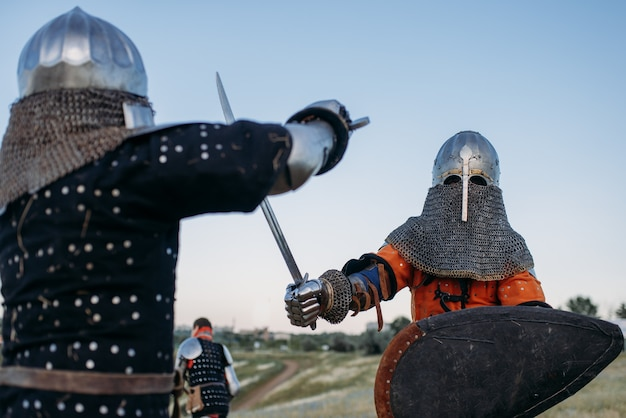 Medieval knights in armour and helmets fight with swords. armored ancient warriors posing in the field