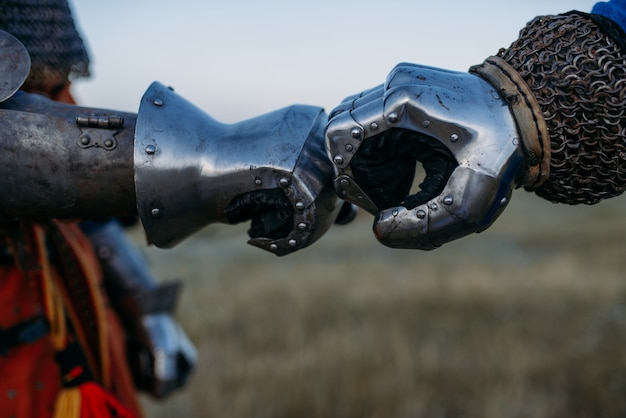 Средневековые рыцари руки в металлических перчатках крупным планом, большой турнир. бронированный древний воин в доспехах позирует в поле