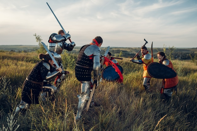 Средневековые рыцари в доспехах и шлемах сражаются мечом и топором. бронированный древний воин в доспехах позирует в поле