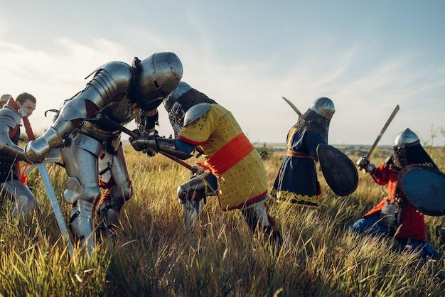 鎧と兜を身に着けた中世の騎士は、剣と斧で戦い、素晴らしい戦いを繰り広げます。フィールドでポーズをとる鎧の鎧の古代の戦士
