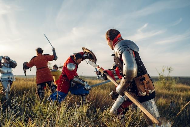 Средневековые рыцари в доспехах, стоящие друг напротив друга перед битвой. бронированный древний воин в доспехах позирует в поле