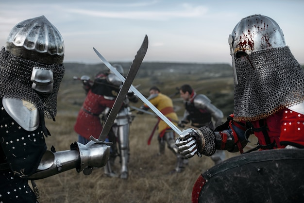 Средневековые рыцари в доспехах и шлемах сражаются на мечах. бронированные древние воины позируют на лугу