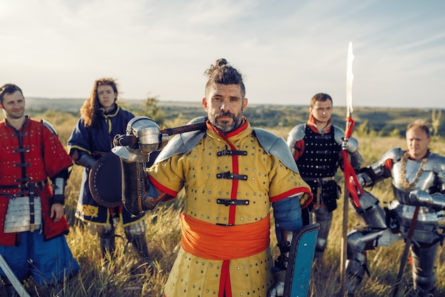 Medieval knights with swords poses in armor, great tournament. armored ancient warriors in armour posing in the field