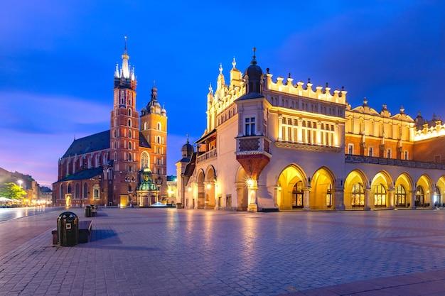 ポーランド、日の出のクラクフ旧市街にある聖マリア大聖堂と織物会館のある中世の中央市場広場