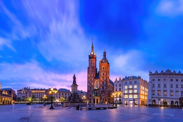 日の出のクラクフ旧市街にある聖マリア大聖堂と織物会館のある中世のメインマーケット広場