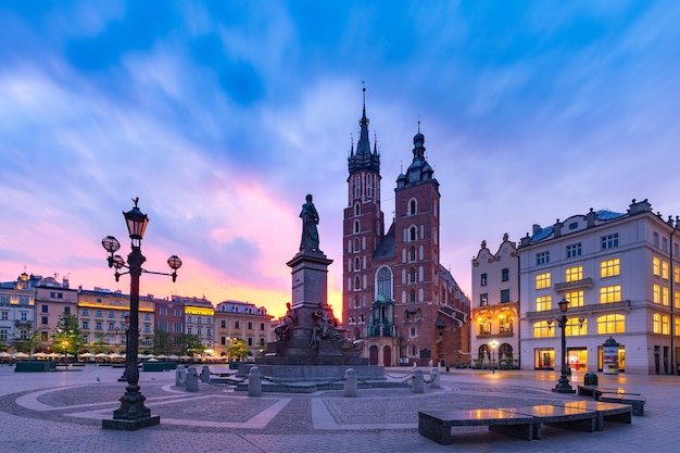 クラクフの旧市街の豪華な日の出に聖マリア大聖堂がある中世のメインマーケット広場