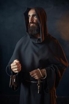 Средневековый монах держит в руках связку ключей