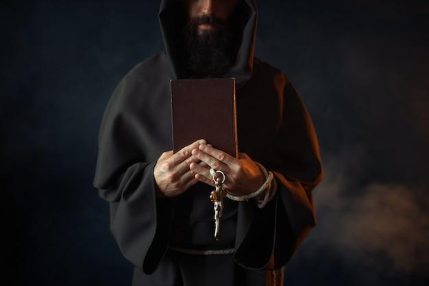 Средневековый монах держит в руках книгу и деревянный крест