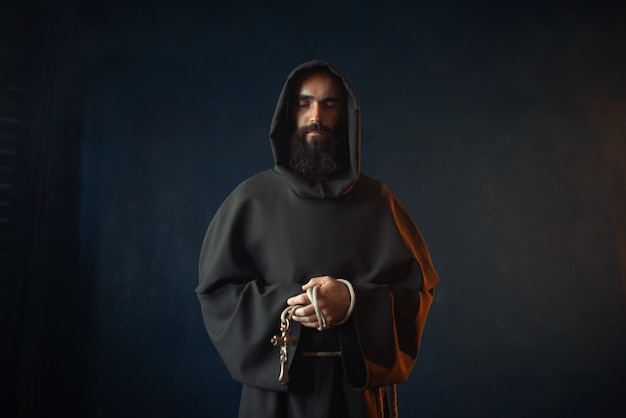 Medieval monk holds cross in hands and praying