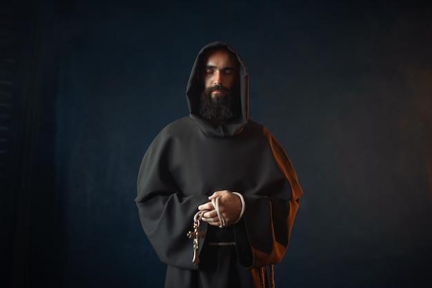 Средневековый монах держит крест в руках и молится