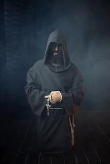 Средневековый монах держит в руках деревянный крест и молится, религия. таинственный монах в темном плаще. тайна и духовность